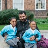father with two daughters in blue cardigans