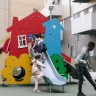big playhouse with slide coming out of the side window